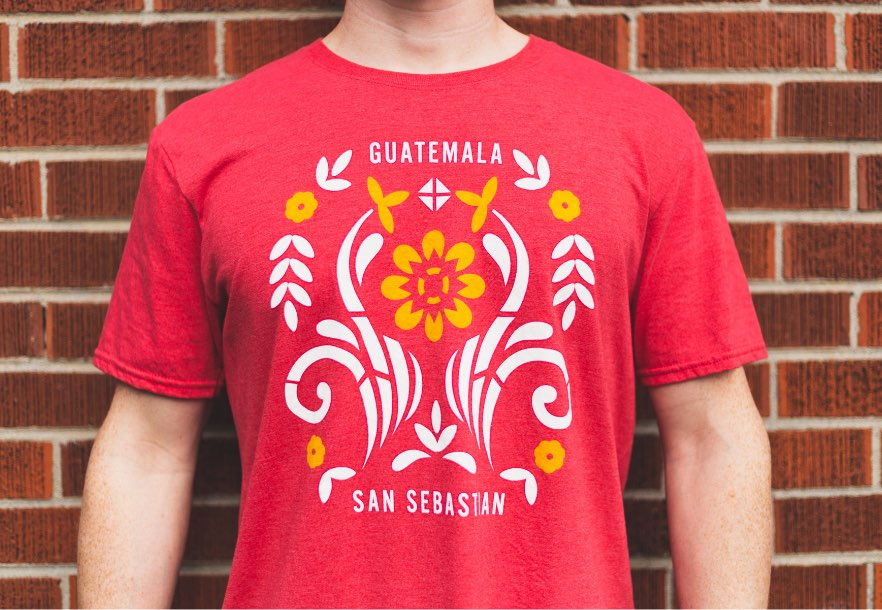 "Man's chest with ""Guatemala/San Sebastian"" screen print on red t shirt"