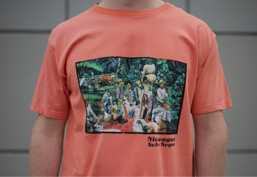 Man's chest with Nicaragua/Selva Negra screen print on salmon tee