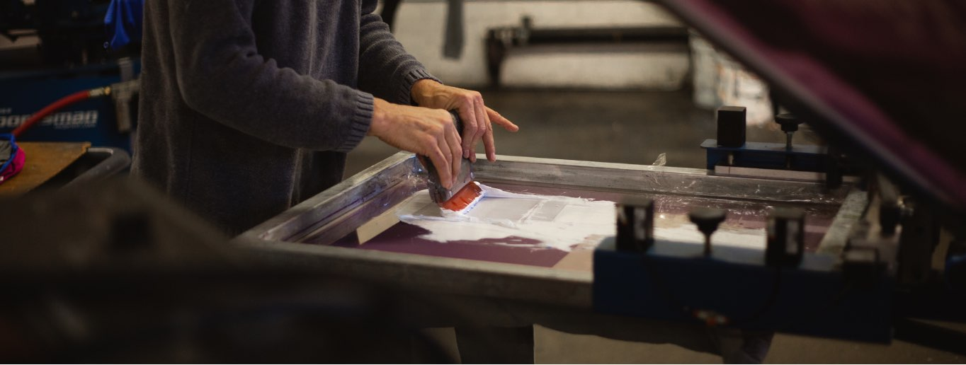 Man using manual screen printer with white ink